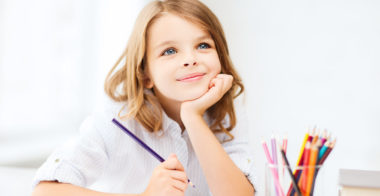 education and school concept - little student girl drawing with pencils at school